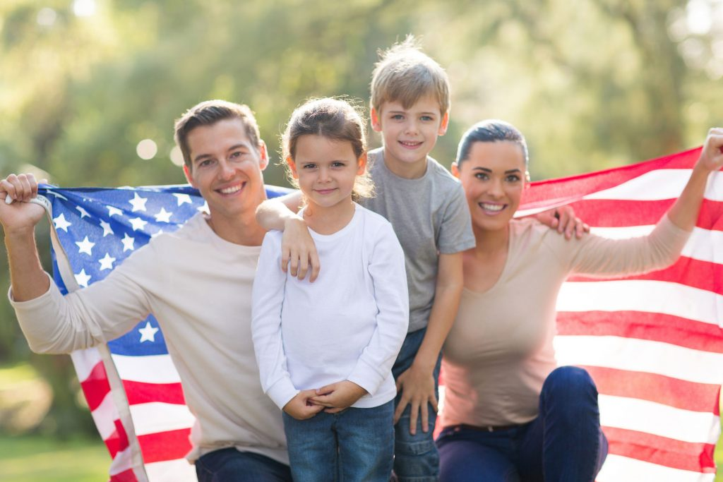 28819279 - portrait of beautiful modern american family with usa flag outdoors
