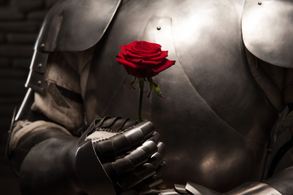 29700215 - closeup portrait of medieval knight in armor holding red rose on dark background, romance concept