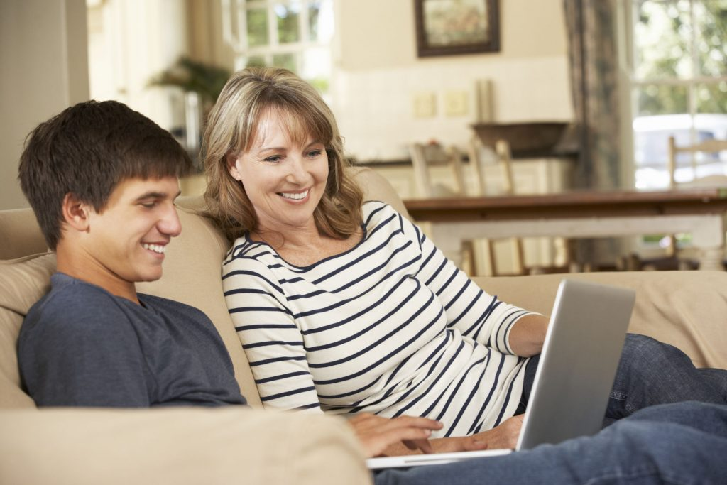 42269892 - mother with teenage son sitting on sofa at home using laptop