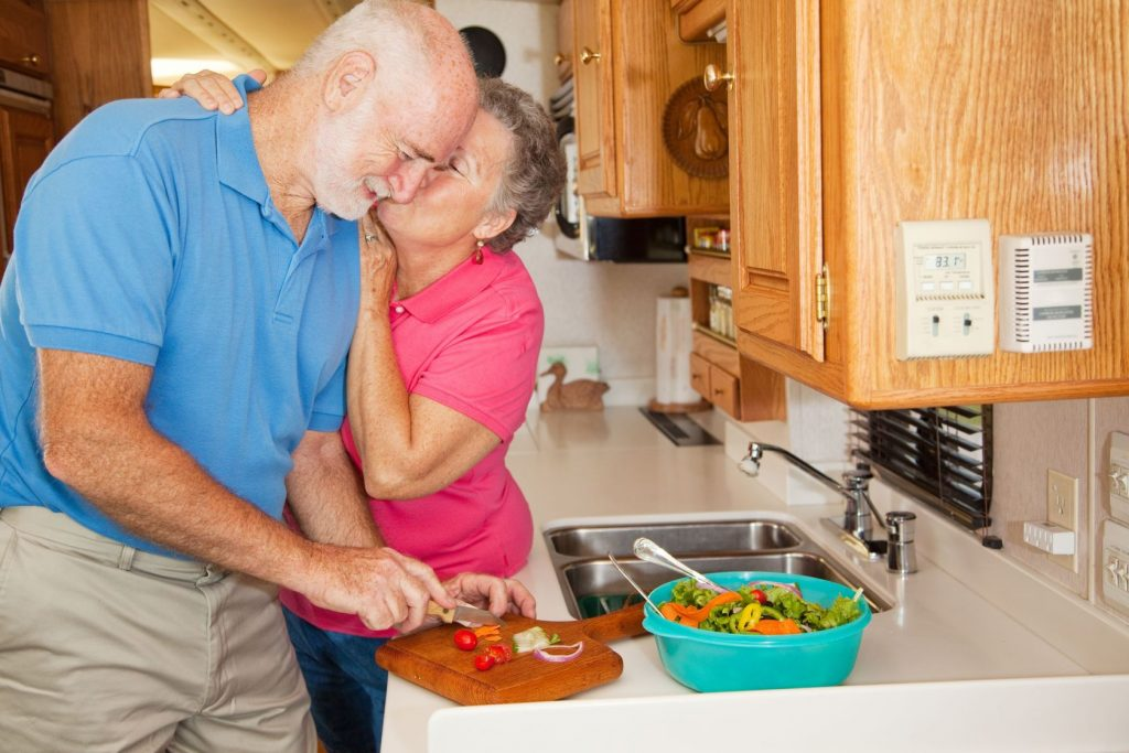 4783925 - senior man helping his wife in the kitchen of their rv gets rewarded with a kiss.
