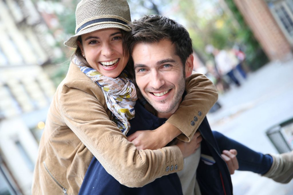 33313091 - man giving piggyback ride to girlfriend, having fun