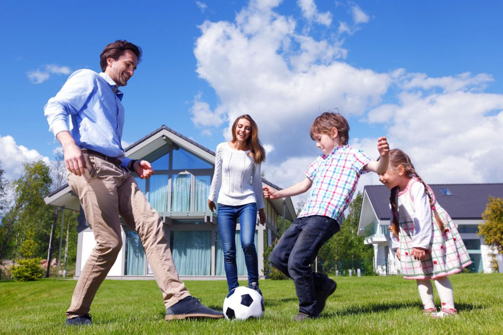41190853 - family playing football in front of their house