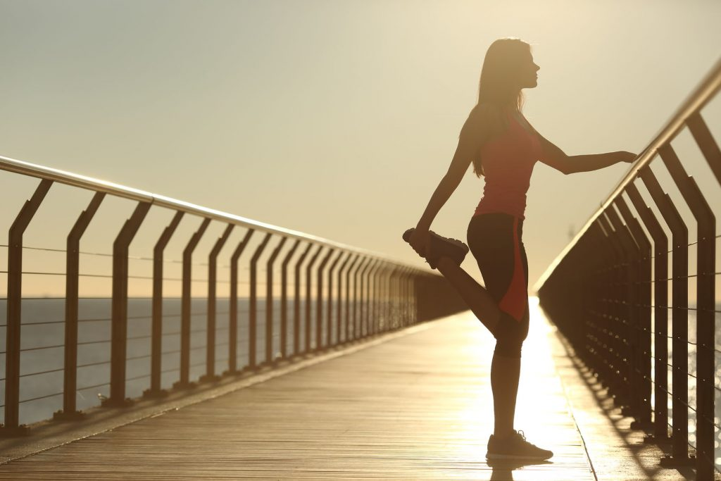 39083244 - woman silhouette exercising stretching on a bridge after running at sunset