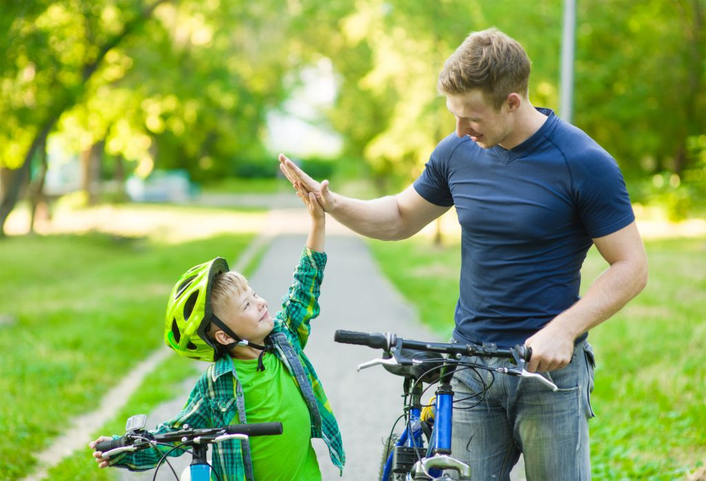 44519860 - father and son give high five while cycling in the park