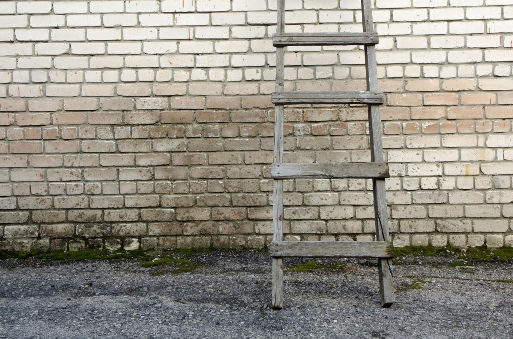 60273715 - old wooden ladder against a wall