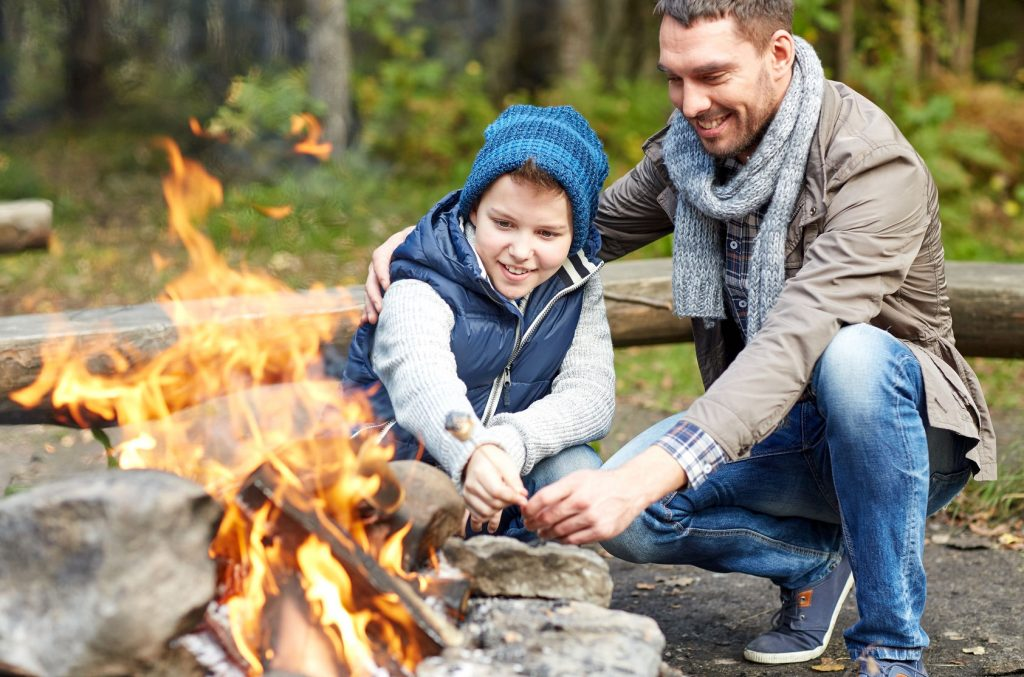 49276455 - camping, tourism, hike, family and people concept - happy father and son roasting marshmallow over campfire