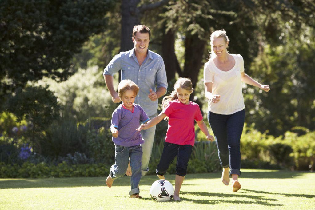 42247826 - family playing football in garden together